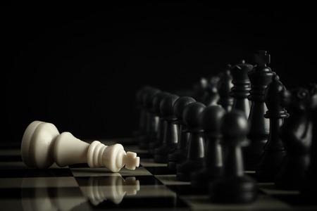 ajedrez: Ej�rcito negro del ajedrez derrota al rey blanco en el tablero de ajedrez. Foto de archivo