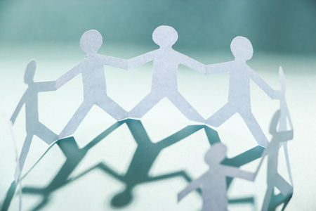 teamwork together: Group of people made of paper are holding hands together. Team concept.