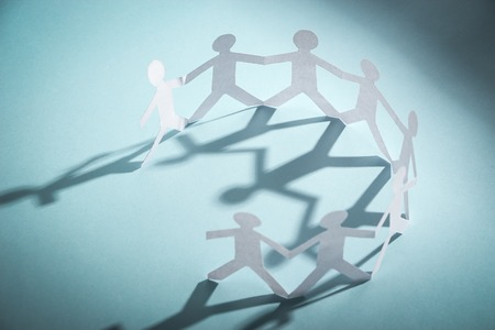 linked together: Group of people made of paper are holding hands together. Team concept.