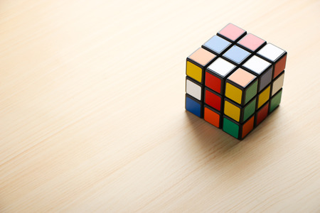 Rubik's Cube is on the table background. Editorial