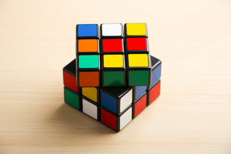 unsolved: Rubiks Cube is on the table background.