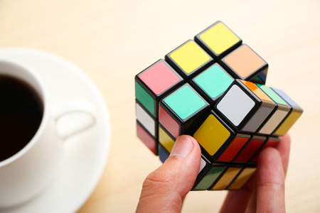 enigma: Rubiks Cube is holden by hand with a cup of coffee aside.