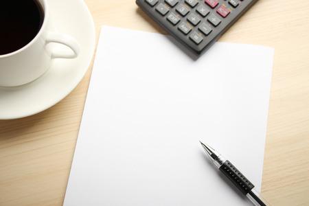 calculadora: Libro Blanco en blanco está sobre la mesa con la calculadora y el café a un lado.