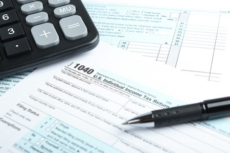 Tax form business financial concept with a pen and a calculator aside. photo