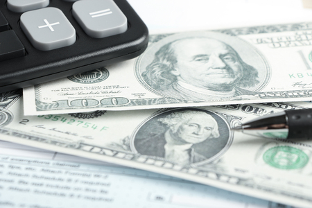 withhold: Dollar and some business objects is on the desk. Stock Photo