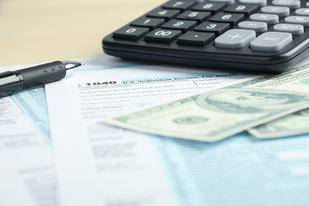 tax form: Tax form financial concept with some money and some other business objects aside.