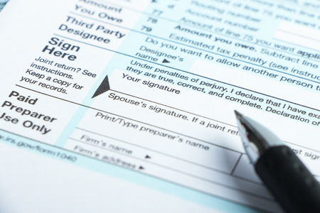 taxable: Sign here of the tax form with a pen aside. Stock Photo
