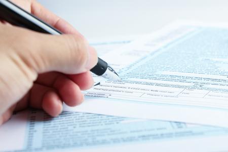Een persoon is het invullen van het belastingformulier met een pen. Stockfoto