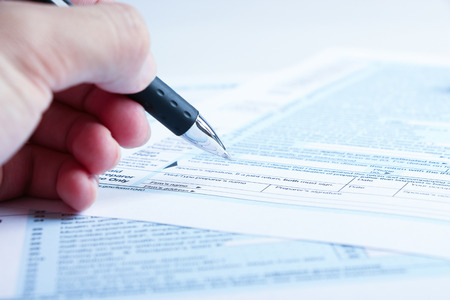 taxable: A person is completing the tax form with a pen.