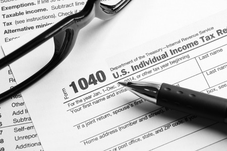 federal tax return: Tax form business financial concept with a pair of black glasses and a pen aside. Stock Photo