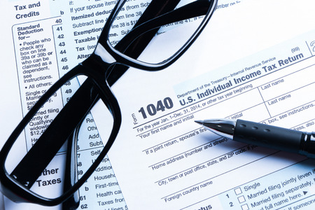 net income: Tax form business financial concept with a pair of black glasses and a pen aside. Stock Photo
