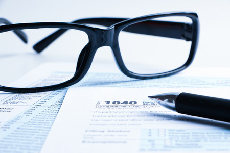 taxable income: Tax form business financial concept with a pair of black glasses and a pen aside. Stock Photo