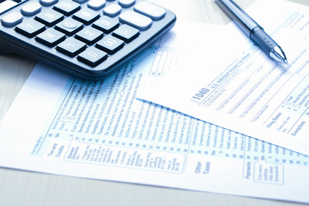 government services: Tax form business financial concept with a pen and a calculator aside. Stock Photo