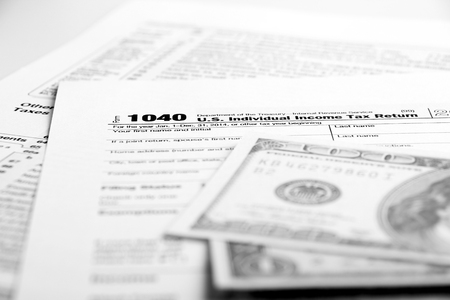 government services: Tax form financial concept with money and some other business objects aside.
