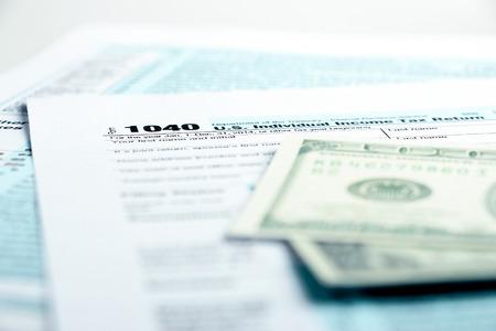arrears: Tax form financial concept with money and some other business objects aside.