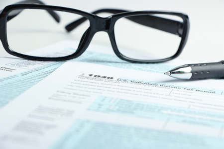 taxpayer: Tax form business financial concept with a pair of black glasses and a pen aside. Stock Photo