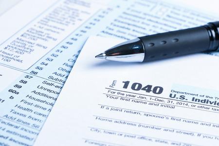 impuestos: concepto financiero formulario de impuestos de negocios con una pluma a un lado.