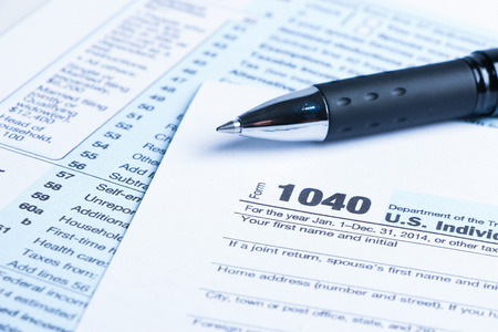 impuestos: Tax form business financial concept with a pen aside.