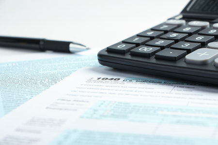 tax form: Tax form business financial concept with a pen and a calculator aside. Stock Photo