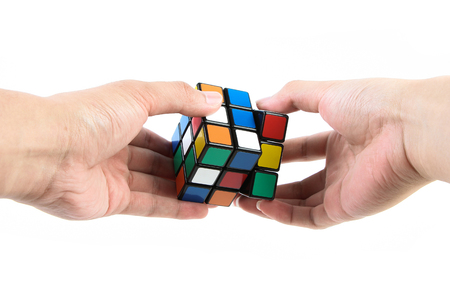 rubik: A man is playing the rubiks cube isolated on white background.