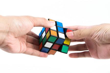 Een man speelt de Rubik's kubus op een witte achtergrond.