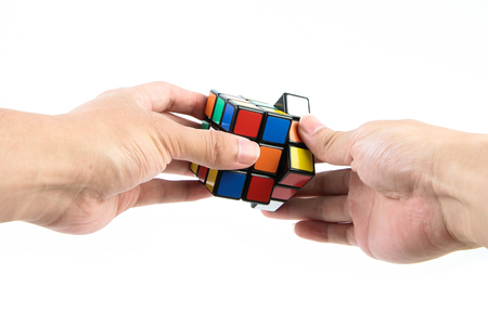 A man is playing the rubik's cube isolated on white background. Reklamní fotografie - 43350076