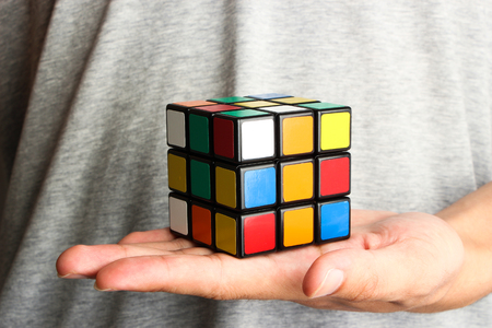unsolved: Rubiks Cube is on the opening hand of a man.