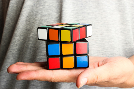 rubik: Rubiks Cube is on the opening hand of a man.