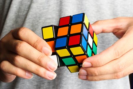 Closeup image of a man playing a rubik's cube. Editoriali