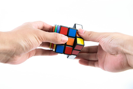 A man is playing the rubik's cube isolated on white background. 에디토리얼