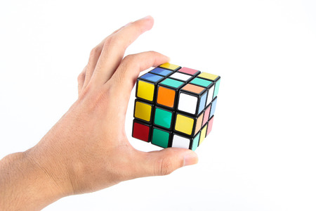 unsolved: Rubiks cube is holden by hand isolated on white background. Editorial