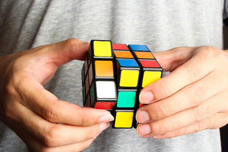 unsolved: Closeup image of a man playing a rubiks cube.