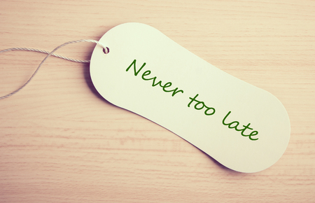 too late: Never too late label is on the wooden desk background.