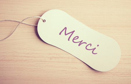 Merci label is on the wooden desk background. photo