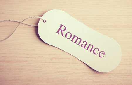 wooden desk: Romance label is on the wooden desk background. Stock Photo