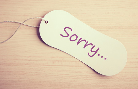 sorry: Sorry label is on the wooden desk background.