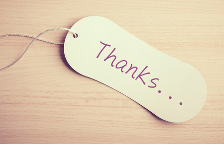 Thanks label is on the wooden desk background. photo