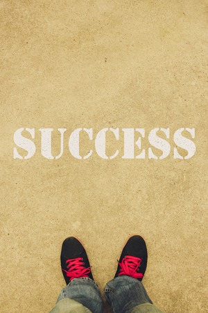 complete crossing: Success text is painted on the ground in front of the feet. Stock Photo