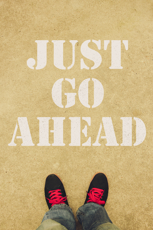 go ahead: Just go ahead text is painted on the ground in front of the feet. Stock Photo