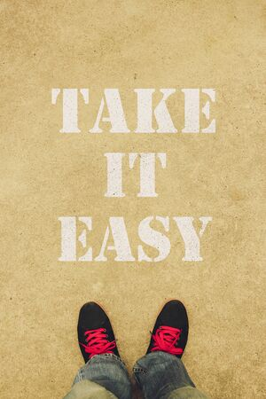 take it easy: Take it easy text is painted on the ground in front of the feet.