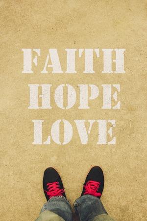 geloof hoop liefde: Geloof, hoop, liefde is de tekst geschilderd op de grond voor de voeten.