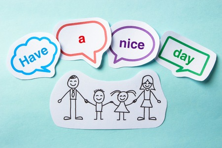 slateboard: Happy paper family with speech bubbles of Have a nice day concept on the blue background.