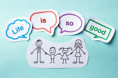 enjoy life: Happy paper family with speech bubbles of Life is so good concept on the blue background. Stock Photo