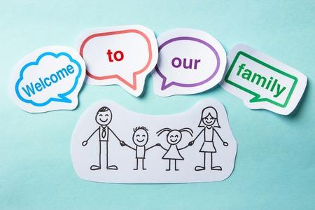 apoyo familiar: Documento de la familia feliz con las burbujas del discurso de bienvenida a nuestro concepto de la familia en el fondo azul. Foto de archivo