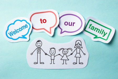 welcome to: Happy paper family with speech bubbles of Welcome to our family concept on the blue background. Stock Photo