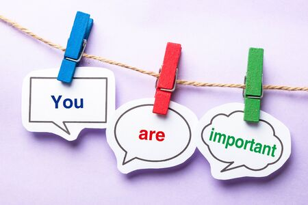 self assurance: You are important paper bubbles with clip hanging on the line against purple background. Stock Photo