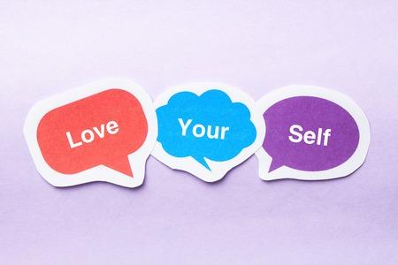 egoistic: Love your self concept paper bubbles against purple background. Stock Photo