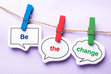 be the change: Be the change paper bubbles with clip hanging on the line against purple background.