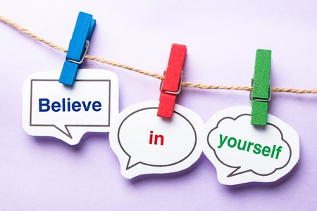 Believe in yourself paper bubbles with clip hanging on the line against purple background.