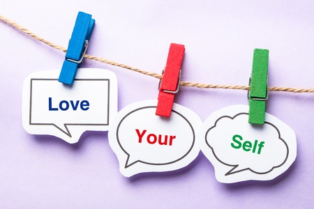yourself: Love your self paper bubbles with clip hanging on the line against purple background. Stock Photo